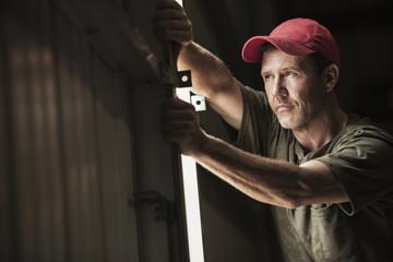 Farm worker closing barn door on sunny day
