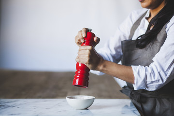 Midsection of woman using pepper mill in kitchen