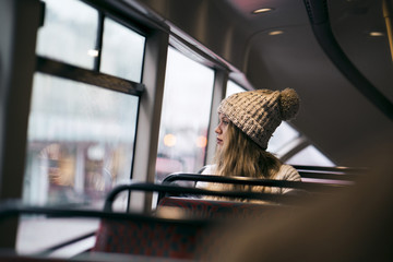 Thoughtful woman looking through window while traveling in bus