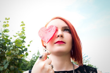 Beautiful red-haired girl covers her eyes with candy in the shape of heart