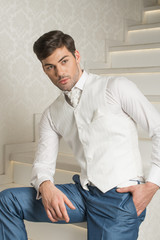 Man model in white shirt, vest and tie sitting on stairs