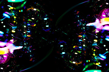 close up of rainbow soap bubbles on black backgrounds.