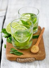 Mojito and ingredients on white wooden surface