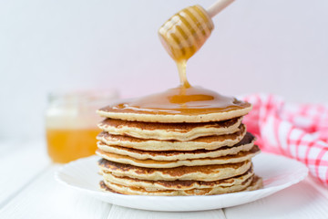 Healthy breakfast. Stack of delicious, homemade pancakes with honey, cherry and banana on white plate