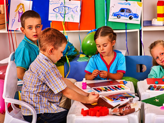 Child dough play in school. Plasticine for children. mold from plasticine in kindergarten .Kids knead modeling clay with hands in preschool. Children's drawings on the walls of classrooms.