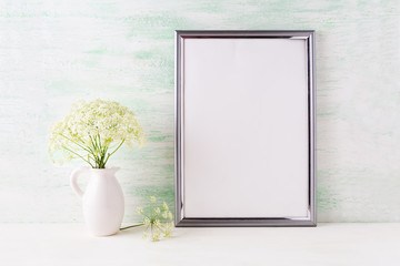 Silver frame mockup with delicate wild field flowers in pitcher