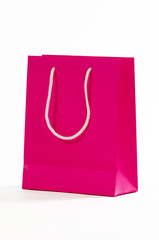 Pink paper bag isolated on white background.