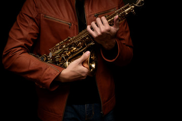 musician saxophone player holding his saxophone on isolated black background.