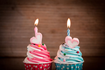 birthday cupcake with sweet heart shape of marshmallow and candle on wooden background