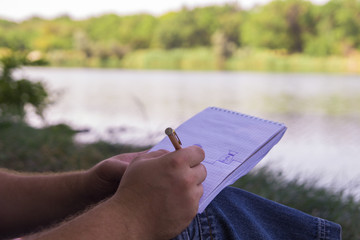 hand writes Notepad pen pencil near the lake in the Park in Sunny day