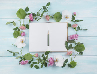 Floral frame consists of roses and orchid flowers and notebook