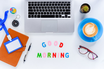 Good morning. Flat lay, top view office desk  table. Workspace with laptop, diary, eyeglasses, compass, pen, blank identification card and cup of coffee on white background.