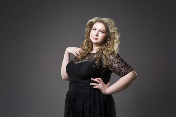 Young beautiful blonde plus size model in black dres, xxl woman portrait on gray studio background