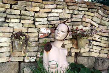 a very strange mannequin in the garden with the flowers