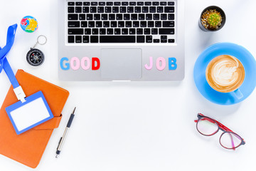 Caption word  Good Job on laptop. White office desk with laptop, diary, eyeglasses, compass, pen, blank identification card and cup of coffee.Top