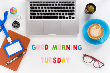 Caption word  Good morning tuesday. White office desk with laptop, diary, eyeglasses, compass, pen, blank identification card and cup of coffee on white background.