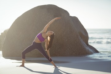 Beautiful woman performing stretching exercise on beach