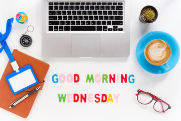 Caption word  Good morning wednesday. White office desk with laptop, diary, eyeglasses, compass, pen, blank identification card and cup of coffee on white background.