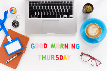 Caption word  Good morning thursday. White office desk with laptop, diary, eyeglasses, compass, pen, blank identification card and cup of coffee on white background.