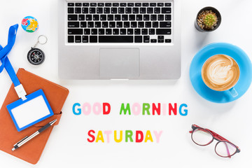 Caption word  Good morning saturday. White office desk with laptop, diary, eyeglasses, compass, pen, blank identification card and cup of coffee on white background.