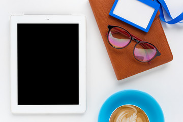 Modern White office desk table with eyeglasses,tablet,notebook,name card and cup of coffee.Top view with copy space.Working desk table concept.