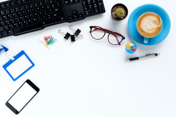 Modern White office desk table with eyeglasses,smart phone,keyboard,name card and cup of coffee.Top view with copy space.Working desk table concept.