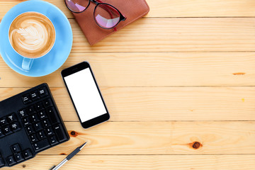 Office desk table with blank screen smartphone,cup of coffee,keyboard,pen,eyeglasses and leather notebook.Top view with copy space.