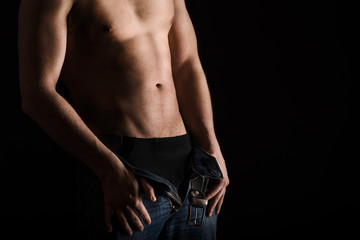 Handsome topless man without face on black background posing in studio