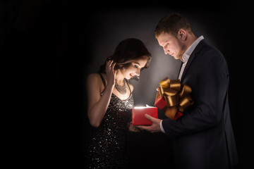 Man and woman opening gift