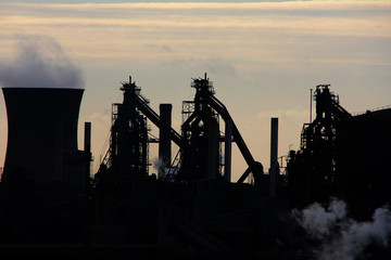 Blast furnaces for bulk iron manufacture in silhouette.