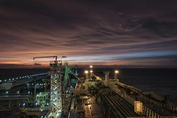 Tanker at berth in port at late sunset.