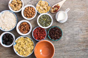 Ingredients for healthy granola: nuts, oats, cereals and dried fruits, top view, selective focus