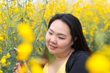 Happy Asian fat woman take photo by her self in flower garden