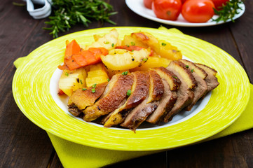 Roast goose breast fillet with potatoes rustic style on a plate on a dark wooden background