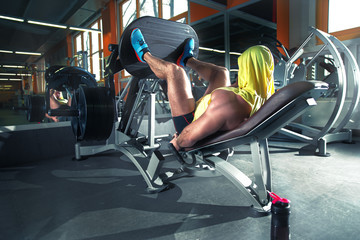 Fitness and Sport. Athletic man doing exercises on legs in gym among other people.