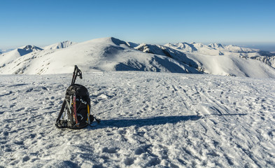 Backpack with ice axes and trekking poles in winter in the mountains.