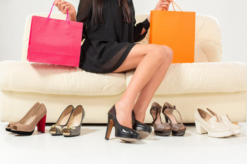Colorful shoes and bags with woman sitting on the sofa.