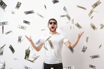 young happy man with a beard in white shirt standing under money