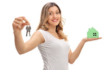 Happy woman holding pair of keys and model house
