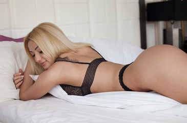 Sexy smiling woman relaxing in bed with lingerie.
