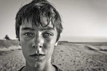 bw portrait of a teenage boy at the beach