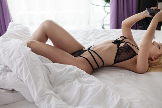 Sexy woman in black lingerie lying on bed write message by phone