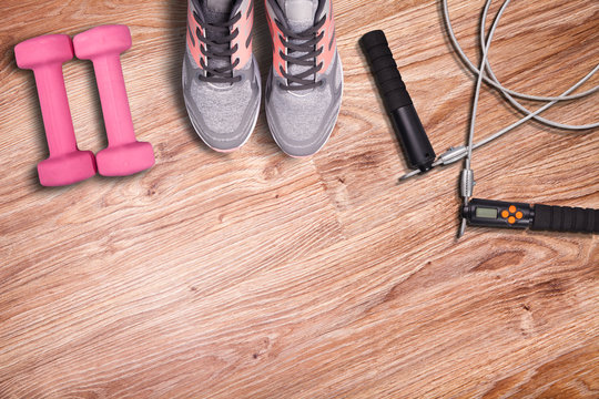 Gym mat and fitness accessories. Sport run shoes and jump rope. Light pink dumbbells on wood floor background.
