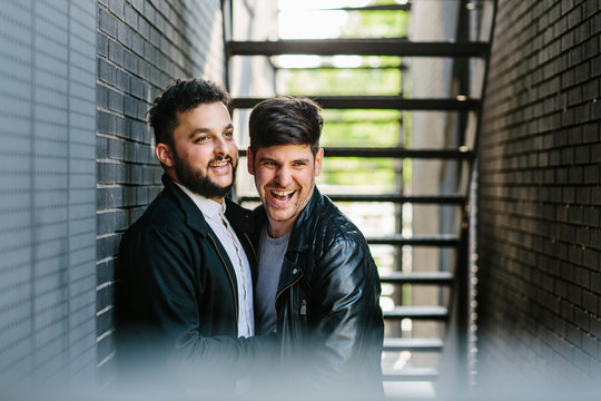 Smiling gay couple standing against wall