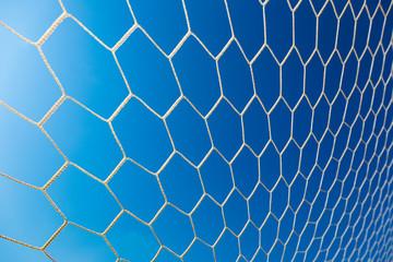 white soccer or football goal net against clear deep blue sky