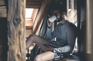 Young man using tablet and drinking coffee at home