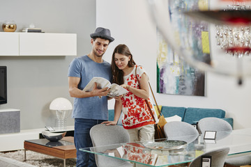 Couple in furniture store looking at dining table, looking at catalogue