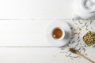 Hot tea with tea pot on white wood background