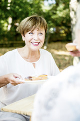 Smiling senior woman offering muffins