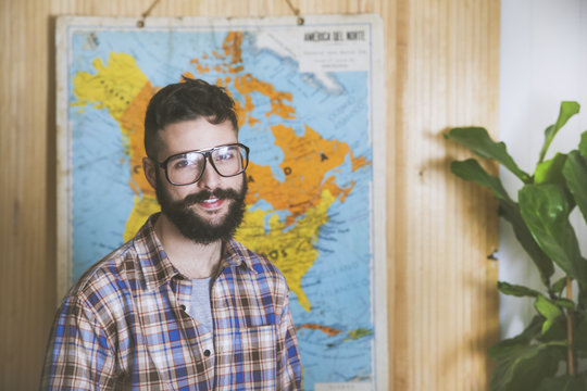 Portrait of bearded man wearing glasses in front of a map